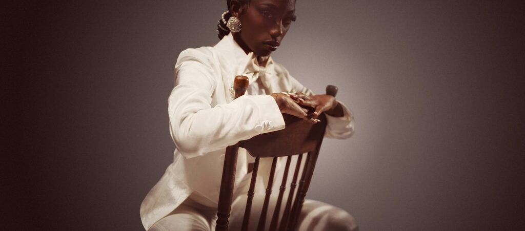 Flo Milli Sits In A Chair Wearing All White. She'S Looking At The Camera.